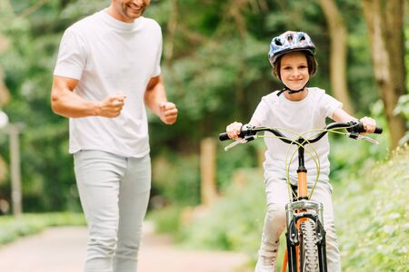cropped view of father cheering son while boy riding bicycle and looking at camera