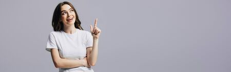 happy beautiful girl in white t-shirt showing idea gesture and looking away isolated on grey, panoramic shot