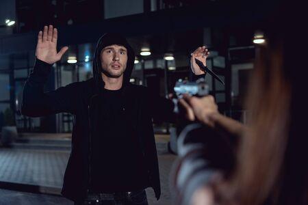 Mujer apuntando con pistola al ladrón con las manos en el aire en el estacionamiento Foto de archivo