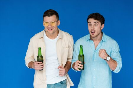 two friends holding bottles of beer and looking away isolated on blue