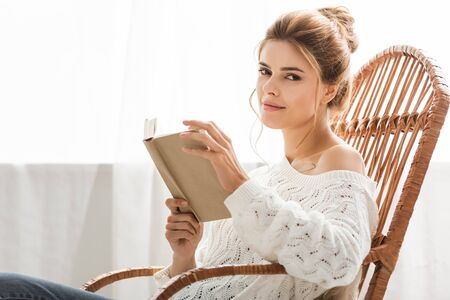 attractive woman in white sweater sitting on rocking chair and holding book Standard-Bild - 130117769