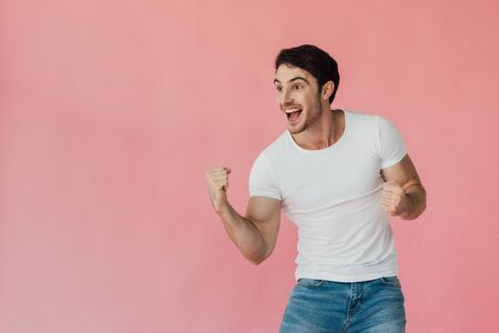 excited muscular man in white t-shirt showing yes gesture isolated on pink