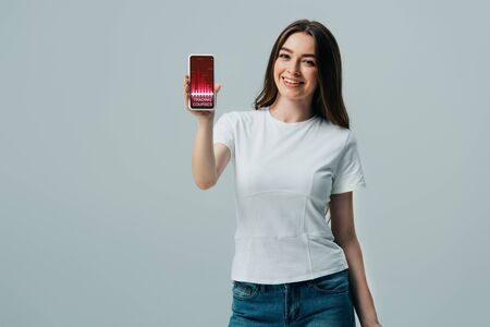 happy beautiful girl in white t-shirt showing smartphone with trading courses app isolated on grey Stock Photo
