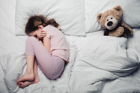 top view of scared child lying on white bedding near teddy bear