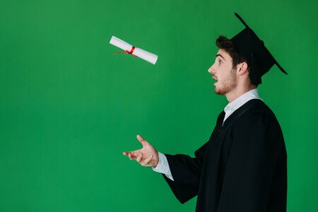 side view of surprised student in academic cap throwing up diploma with red ribbon isolated on green