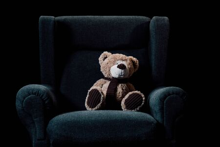 beige teddy bear in grey soft armchair isolated on black Stock Photo