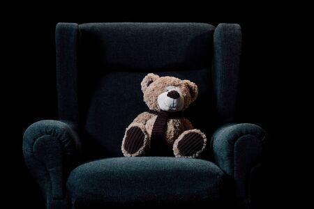 beige teddy bear in grey soft armchair isolated on black Reklamní fotografie