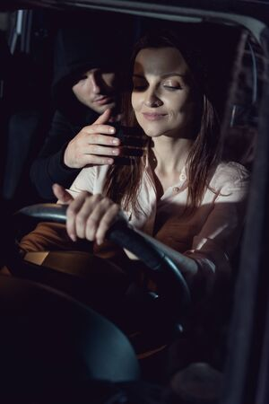 thief hiding on backseat near beautiful smiling woman