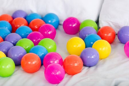 Bright colorful toy balls scattered on white sheets Banco de Imagens