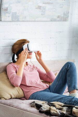 young adult woman playing with virtual reality headset in apartment Banco de Imagens