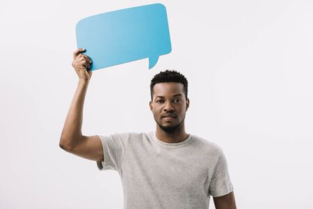 handsome african american man holding blue speech bubble isolated on white Stock Photo