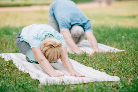 man and woman practicing relaxation yoga poses on yoga mats in park Stockfoto