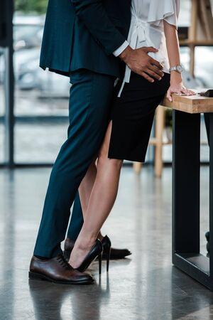 Ausgeschnittene Ansicht eines Geschäftsmannes, der beim Flirten im Büro steht und eine Geschäftsfrau berührt