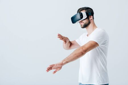 bearded man in Virtual reality headset gesturing isolated on grey
