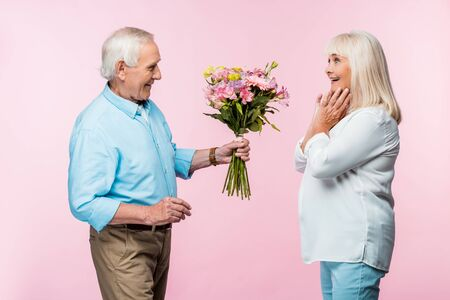 cheerful senior man giving bouquet with flowers to excited wife on pink