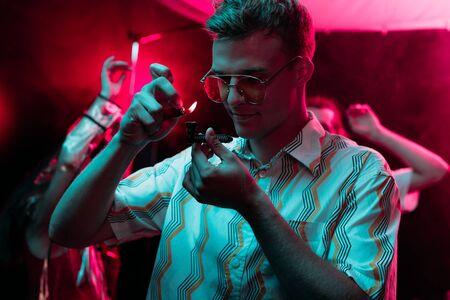 man lighting smoking pipe with marijuana in nightclub Imagens