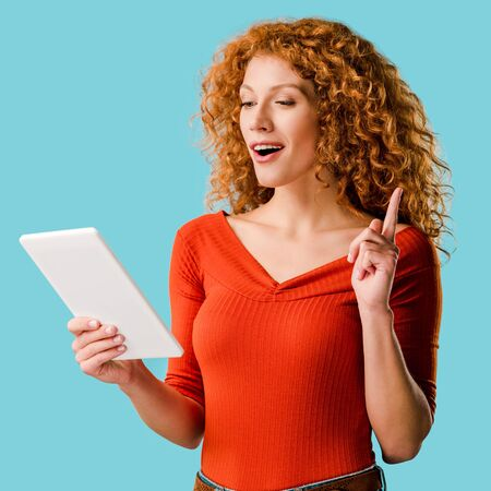woman using digital tablet, pointing up and having idea isolated on blue Stock Photo