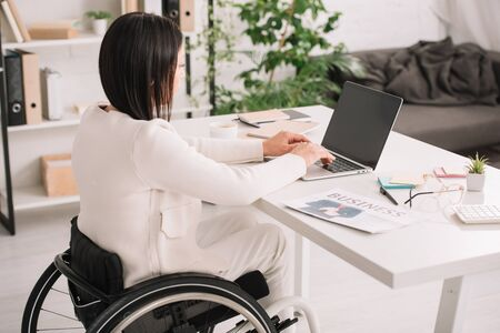 young disabled businesswoman using laptop while sitting in wheelchair at workplace Stock Photo