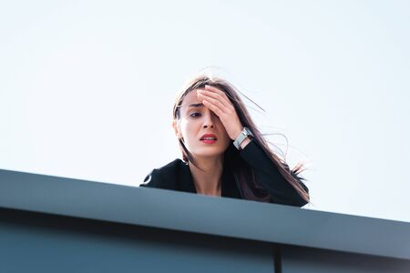 frightened businesswoman, suffering from acrophobia, looking down rooftop and covering face with hand