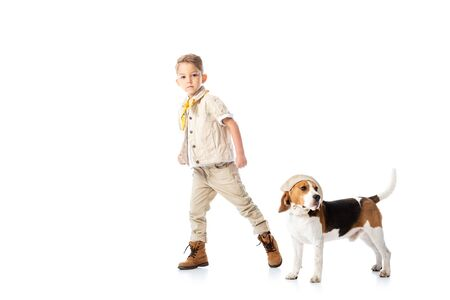 full length view of explorer kid and beagle dog in hat on white