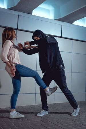 woman defending herself from attacking thief in black hoodie in underpass