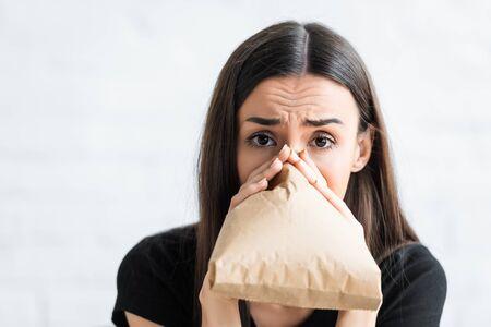 bange vrouw die in een papieren zak ademt en naar de camera kijkt terwijl ze thuis aan paniekaanvallen lijdt