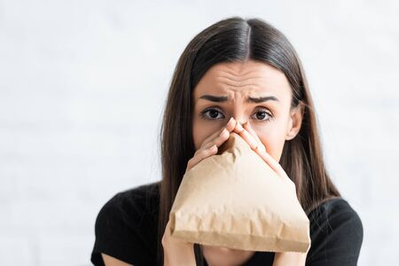 Mujer asustada respirando en una bolsa de papel y mirando a la cámara que sufre de ataque de pánico en casa