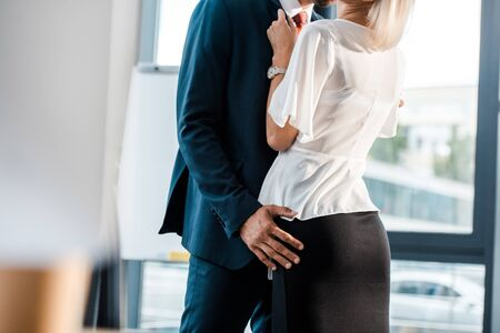cropped view of businessman touching of coworker in office