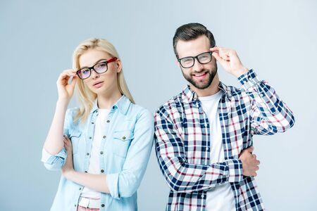 man and girl adjusting glasses and looking at camera on grey