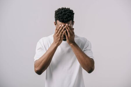 african american man in white t-shirt covering face with hands isolated on grey