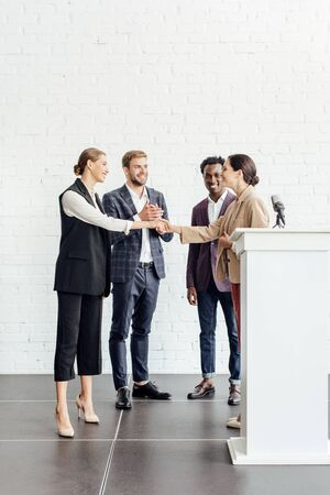 four multiethnic colleagues in formal wear talking and shaking hands