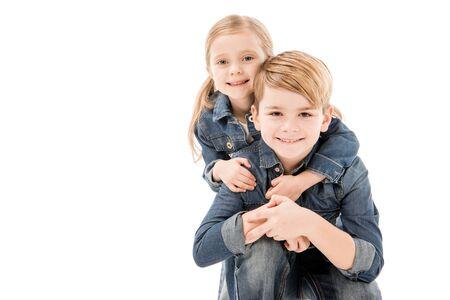 Niños felices abrazándose y mirando a la cámara aislada en blanco