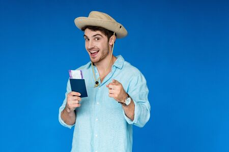 smiling tourist in safari hat holding passport and air ticket and pointing with finger at camera isolated on blue