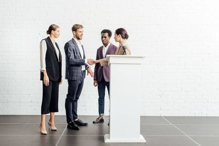four multiethnic colleagues in formal wear talking and shaking hands in conference hall