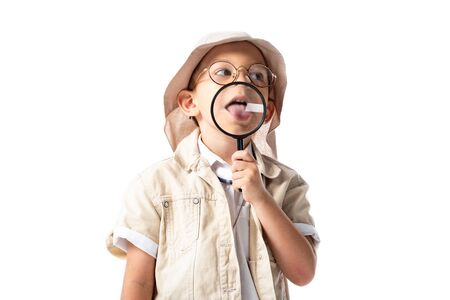explorer child in hat and glasses holding magnifying glass and sticking out tongue isolated on white
