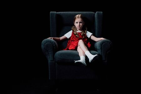 lonely child sitting in armchair and looking at camera isolated on black