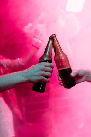 cropped view of men clinking with beer bottles in nightclub Фото со стока