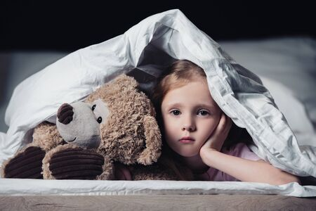 frightened kid looking at camera while lying with teddy bear under blanket isolated on black