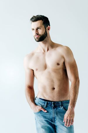 shirtless handsome man in jeans posing with hand in pocket on grey