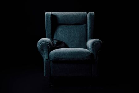 grey, soft armchair isolated on black with lightening