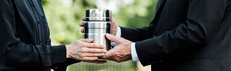 panoramic shot of senior man and woman holding mortuary urn