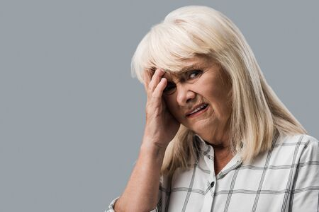 tired and upset retired woman touching head and looking at camera isolated on grey