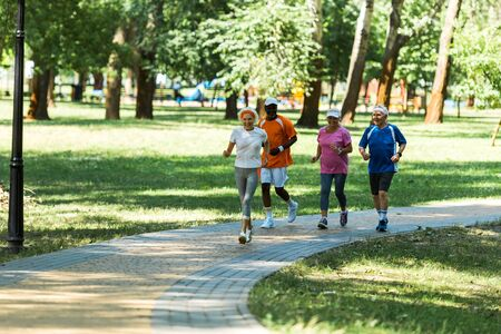 selective focus multicultural retired men and women in sportswear jogging in walkway in park Foto de archivo - 130212622