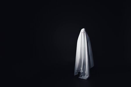 frightening ghost in white bedsheet isolated on black with copy space Фото со стока