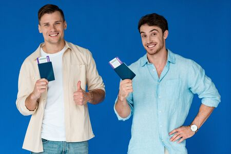 two smiling tourists holding passports with air tickets and showing thumb up isolated on blue 写真素材