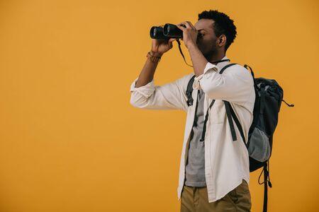 Afroamerikanischer Mann, der durch ein Fernglas isoliert auf Orange schaut