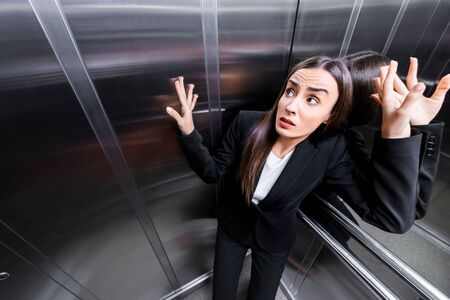young scared businesswoman suffering from claustrophobia in elevator