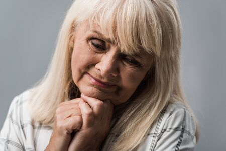 sad retired woman with clenched hands isolated on grey Stockfoto