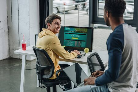 KYIV, UKRAINE - JULY 29, 2019: smiling programmer using computer with Sportsbet website on screen while his african american colleague sitting on desk with laptop
