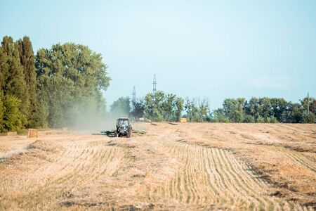 selective focus of modern tractor on wheat field near green trees